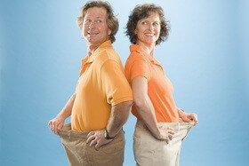 Weightloss couple standing back-to-back
